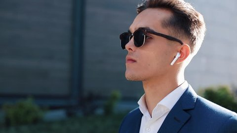 Young businessman with sunglasses listening to the music on his smartphone outdoors. He walking near office building. Communication, audiobooks, music, business people. Shot on Red Epic