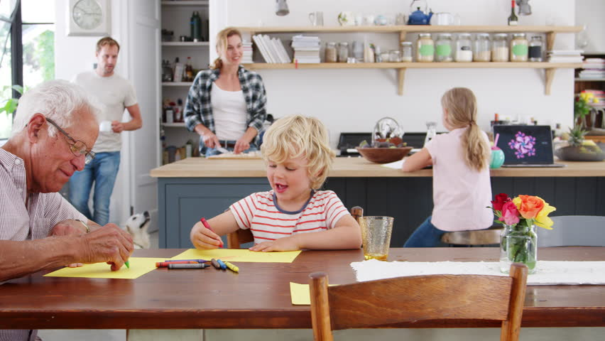 Grandad and grandson drawing together in busy family kitchen