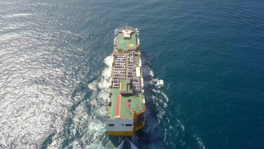 Aerial footage of a Large RoRo (Roll on/off) Vehicle carrier vessel cruising the Mediterranean sea.