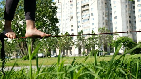 European girl is walking on a tight line in a city park. Woman balancing on slackline, close-up