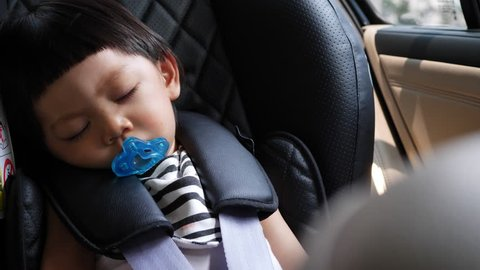 cute child sleeping in car seat