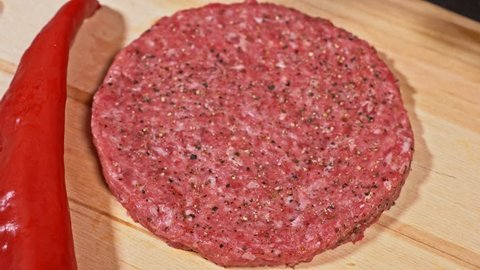 Cook makes meat medallions for burgers. Pouring spices pepper and salt. Meat marbled beef lies on food wooden board for cutting and red pepper chili. Chef in black food gloves makes cutlet medallion.