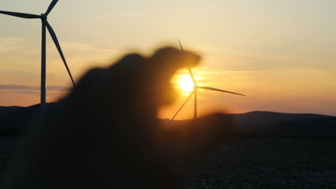 closeup view of unfocused human hand moving against of amazing fiery sunset on a horizon and wind turbines in motion on backfround future generation natural resources minimal human influence