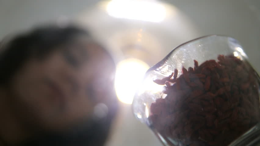 Young woman scattering goji berries in a glass bowl