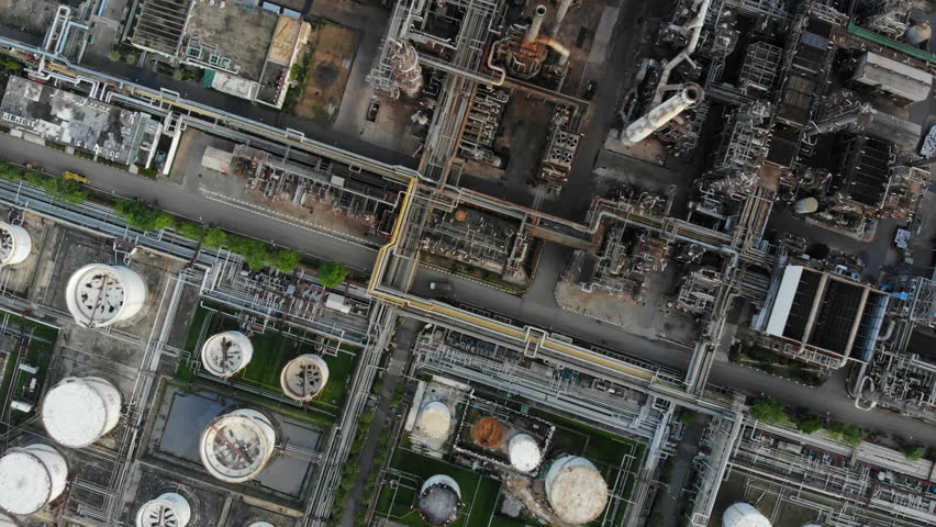 Aerial top down view over oil refinery or chemical factory and power plant with many storage tanks and pipelines. Shot with 4K UHD resolution drone. | Shutterstock HD Video #1012510595