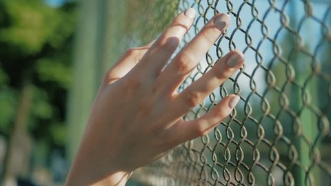 Female hand moving along the surface of grid. Arm of young woman touching metal wire fence. Girl walking during summer vacation and leading his fingers along the guard of bridge. Close up Slow motion