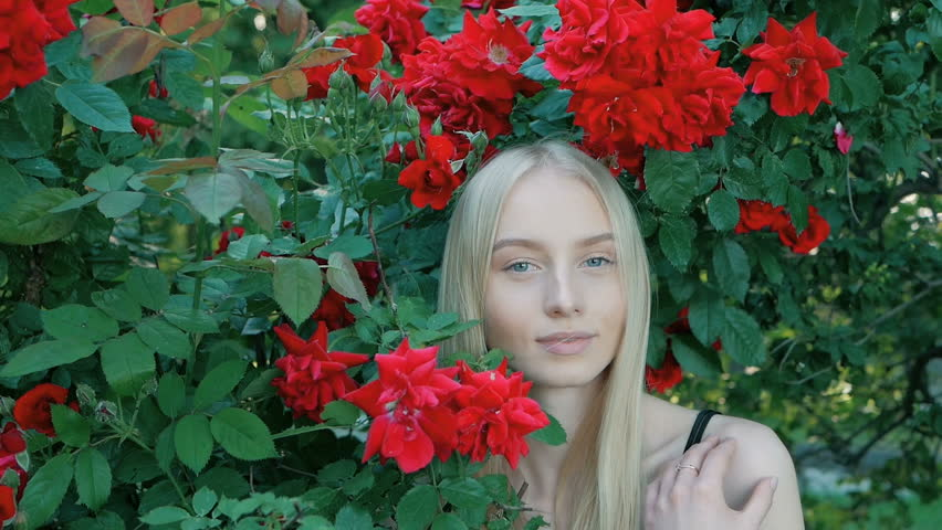 Beautiful fashionable portrait of a young woman with blue eyes and blonde hair in a outdoors in red rose garden | Shutterstock HD Video #1012515845