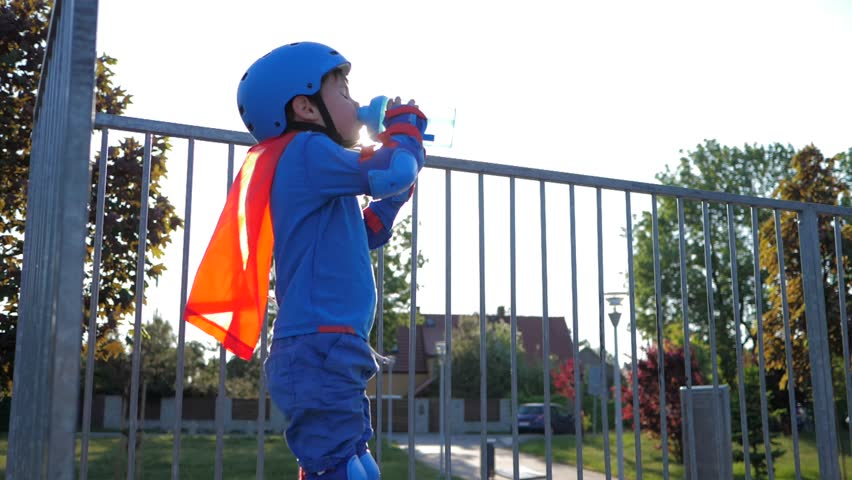 thirst quenching, child in helmet with plastic container in arms drinks mineral water on open air close-up