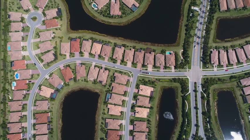 Aerial shot of homes in a residential area in the suburbs of Florida. Aerial view of waterside houses in a gated community.