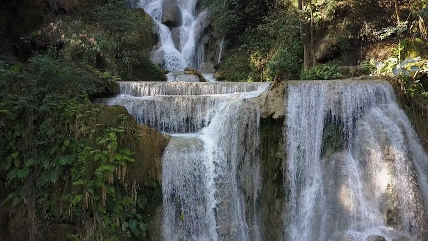 Kuang Si Waterfall details. Drone shot descending down the cascade falls.