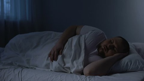 Fat sleeping man tossing in bed, health problem caused by excess weight, apnoe