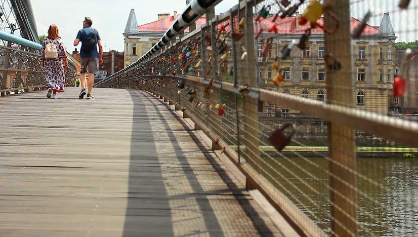 People pass along the bridge with love locks