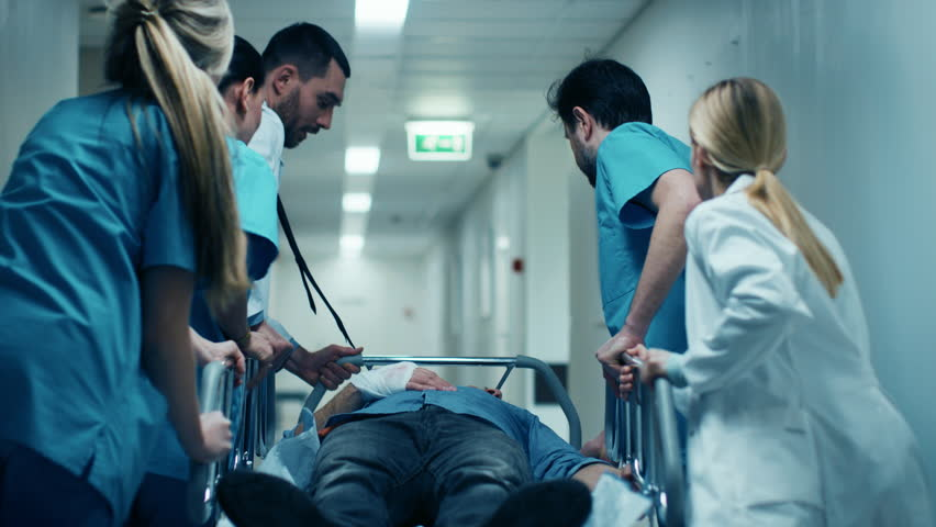 Emergency Department: Doctors, Nurses and Surgeons Move Seriously Injured Patient Lying on a Stretcher Through Hospital Corridors. Medical Staff in a Hurry Move Patient into Operating Theater. 4k UHD. #1012593905