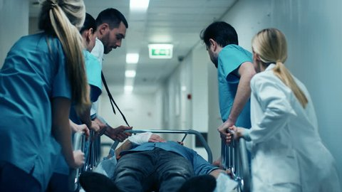 Emergency Department: Doctors, Nurses and Surgeons Move Seriously Injured Patient Lying on a Stretcher Through Hospital Corridors. Medical Staff in a Hurry Move Patient into Operating Theater. 4k UHD.