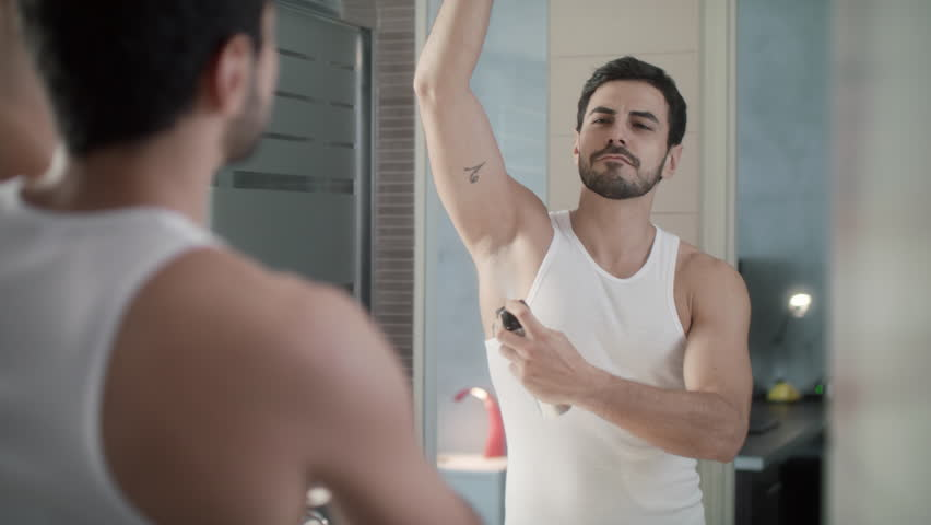 Young hispanic people and male beauty. Confident metrosexual man using spray deodorant on underarm skin, smiling and looking at mirror. Slow motion