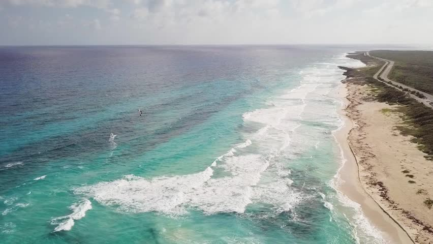 Aerial view in a sliding climb from left to right of a beach on the east coast of Cozumel Mexico. The highway that runs the length of the east coast can be seen.