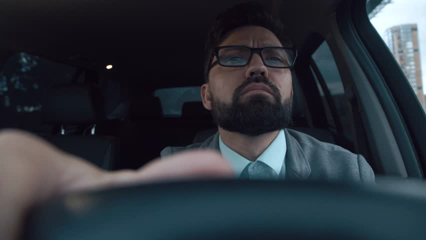 Successful man sits in the car behind the wheel in a traffic jam. Attractive driver is waiting for a traffic light change. Young man with a beard and glasses behind the wheel of a good car. Portrait