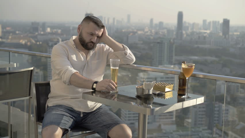 Sad man sitting in skybar and drinking beer   | Shutterstock HD Video #1012677875