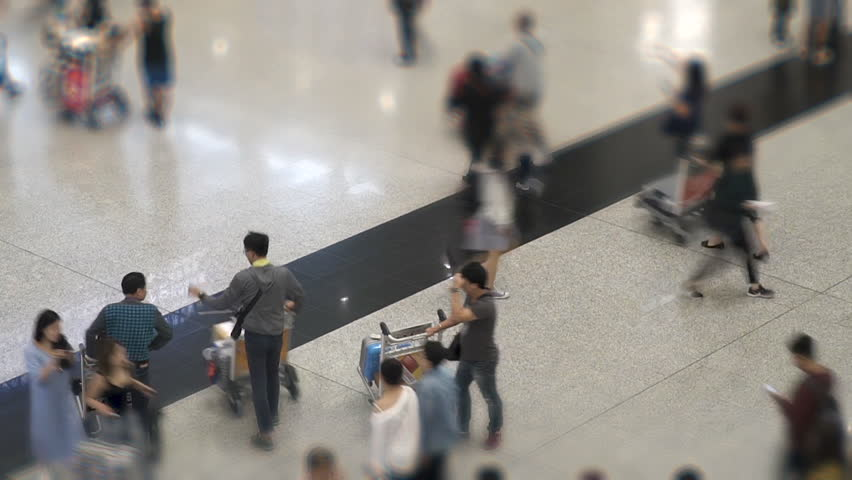 Time lapse of crowd of unrecognizable people walking with luggage in the international airport. Travellers tourists in Hong Kong Airport Terminal