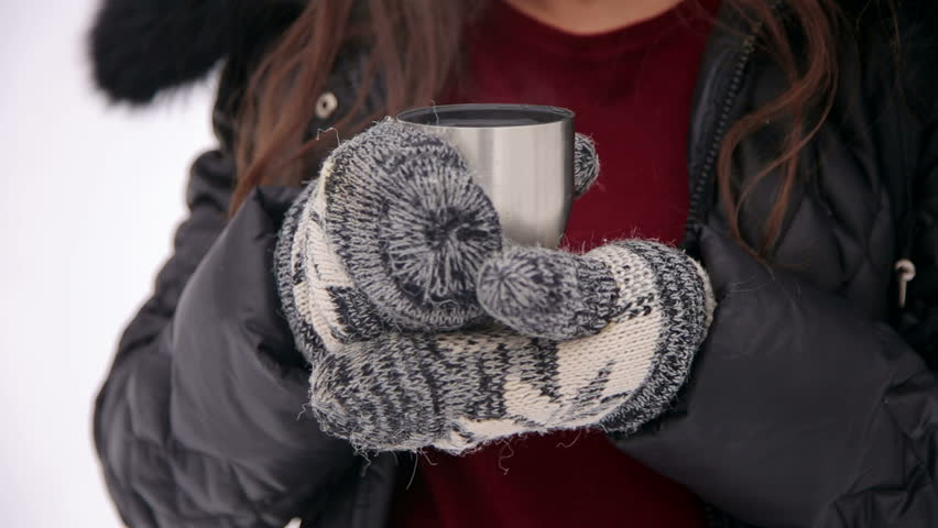 Close-up of a pregnant girl in knitted mittens holding a Cup of hot tea in the winter on the street. Girl drinking tea from a thermos in the cold season, close-up.