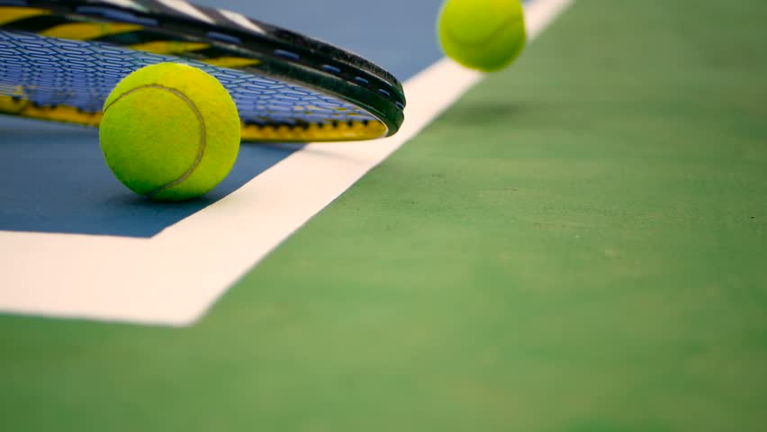 Close up of tennis equipment on the court. Sport, recreation concept. Yellow racket with a tennis ball in motion on a clay green blue court next to the white line with copy space and soft focus. | Shutterstock HD Video #1012707275