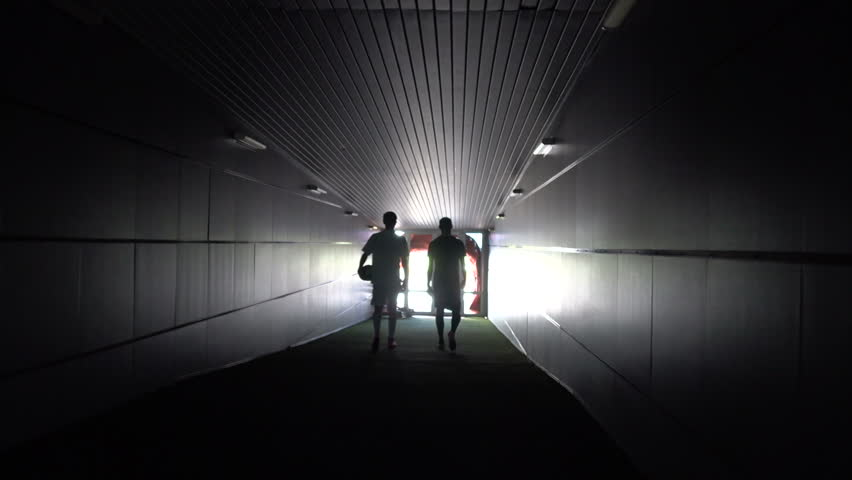 Two football players are walking along a dark tunnel to the football field. View from the back | Shutterstock HD Video #1012709465