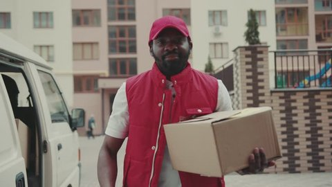 Portrait handsome courier young african american man with cap look at camera smile hold box delivery postal uniform job worker cardboard post distribution transport package logistic