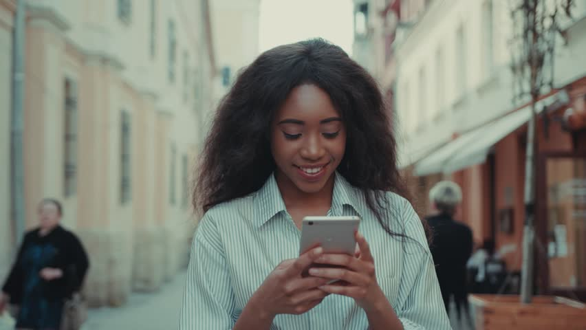 Cheerful young woman walks in the city, uses her smarpthone for online messaging, sending sms. Being online, contemporary devices, communication, chatting. Female portrait | Shutterstock HD Video #1012721795