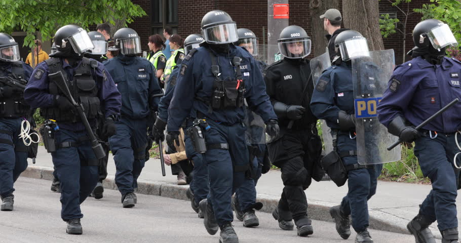 Quebec, Canada - June 2018 - Riot police line marching ahead while tactical baton on their shield.
