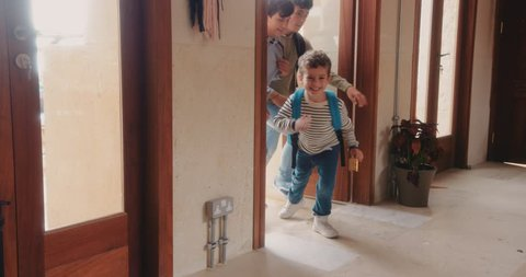 Young brothers racing through house front door when returning back home from school