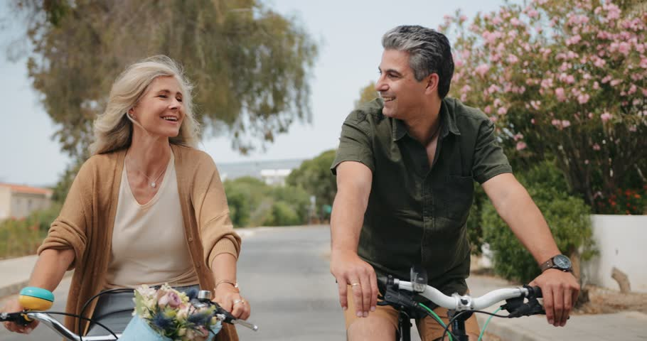 Mature husband and wife cycling and having fun on bikes in the suburbs