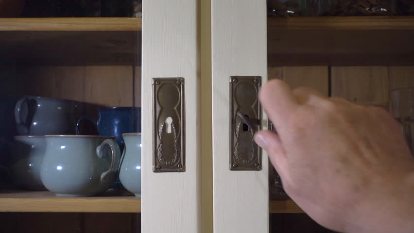Closeup slow motion shot of a man's hand turning a key and opening one of the doors of an old glass fronted, pine kitchen wall cupboard, holding crockery, then removing two drinking glasses.