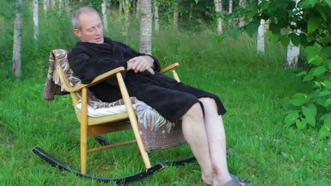 Senior man in bath robe sleeping in rocking chair outdoors