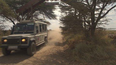 SERENGETI, TANZANIA - JUNE 10, 2016CLOSE UP: All terrain safari jeep full of tourists exiting Serengeti National Park gate and ending private game drive tourist tour in beautiful Tanzania, Africa.