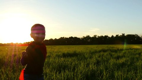 A happy child in a superhero costume in a red raincoat runs along a green lawn against the backdrop of a sunset toward the camera