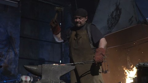 The smith beats metal with a sledgehammer