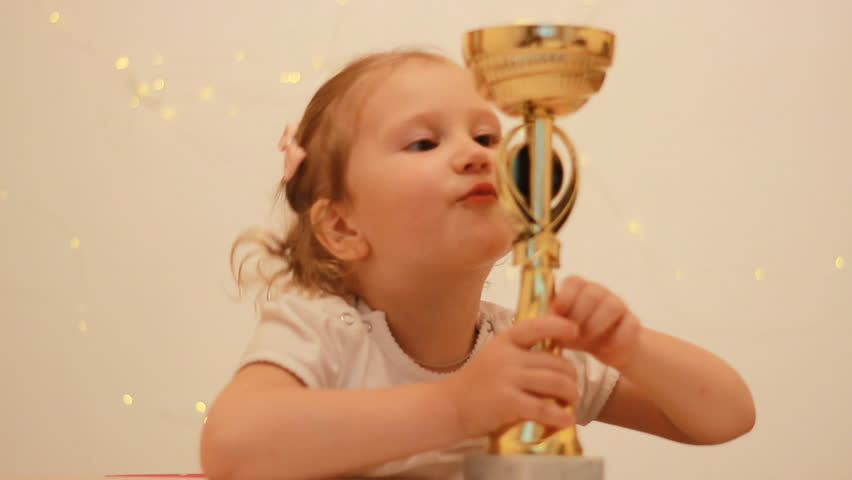 Child girl rejoices in the victory and reward, kisses and hugs the winner's cup for the first place in the championship competition