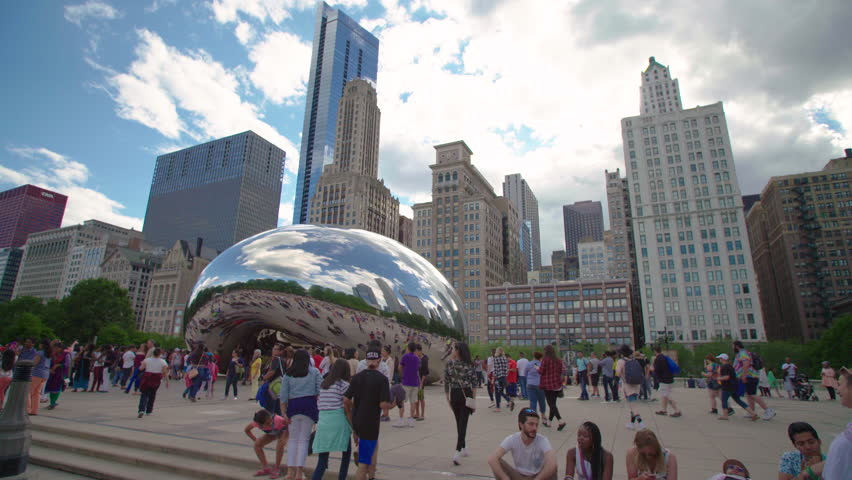 CHICAGO, USA - JUNE 25 20137 People walking around the famous Chicago Cloud Gate, The Bean Sculpture, with the Chicago skyline in the background. | Shutterstock HD Video #1012812395