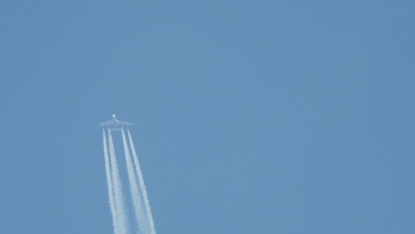 Airplane in flight, making a white stripe in the blue sky, called a contrail, condense trail or vapour trail | Shutterstock HD Video #1012828325