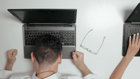 Sales manager is very nervous of working, top view. Frustrated worker starts to bang in head on laptop.