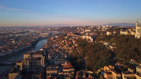 lyon city aerial view at sunrise flying from center to notre dame basilica