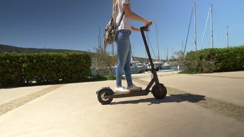 Mid shot - Female riding electric scooter through marina. Modern transportation gadget and popular futuristic device among young people
