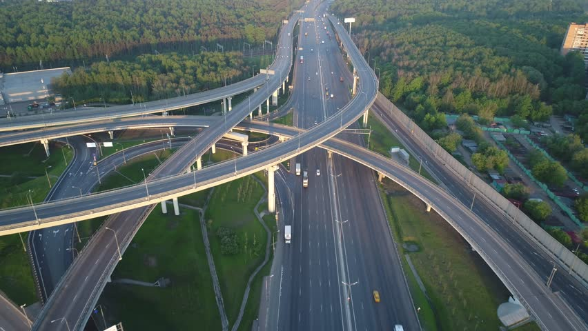 Aerial view. Flyght over a huge interchange of the Moscow ring road in the early morning at dawn. Cars are moving on a multi-level road junction.Highway are free for them moves few cars. | Shutterstock HD Video #1012887485