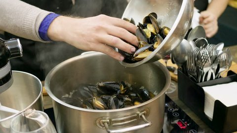 Close-up shot of mussels are being stewed in a saucepan on an electric stove. 4K