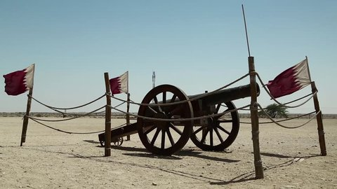 Cannon and flags of Qatar near Al Zubara Fort or Al Zubarah Fort - historic Qatari military fortress built in the time of Sheikh Abdullah bin Jassim Al Thani in 1938, Persian Gulf, Arabian Peninsula