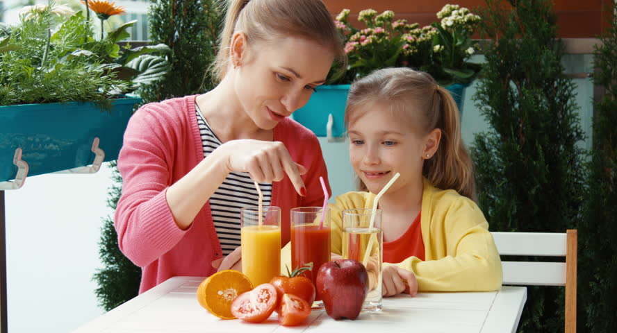 Happy family promoting healthy juice and looking at camera | Shutterstock HD Video #10129175