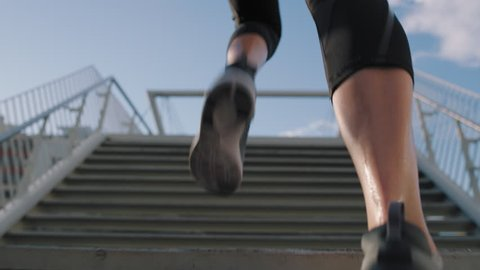 woman athlete feet running up stairs training intense cardio workout exercise male runner legs jogging on steps in urban city background slow motion