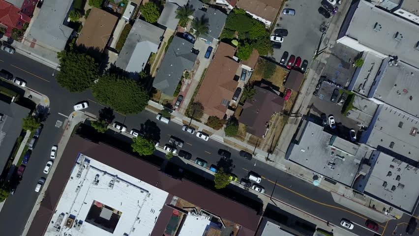An overhead (bird's eye) view of a drone flight over a busy city neighborhood.   Shutterstock HD Video #1012939805