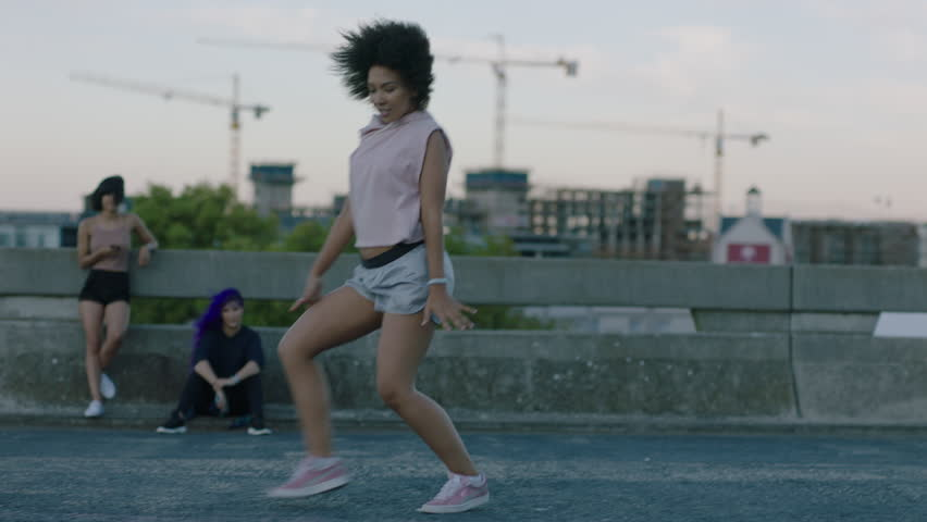 Dancing woman attractive young mixed race dancer performing urban style street dance in city practicing freestyle moves friends watching enjoying hang out at sunset | Shutterstock HD Video #1012940075