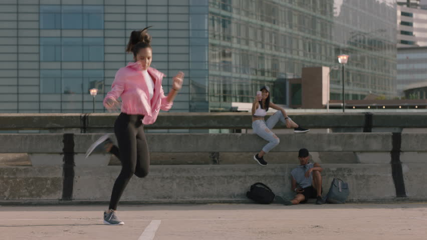 Dancing woman young hip hop dancer performing freestyle moves multi ethnic friends watching enjoying urban dance practice using smartphone taking video sharing on social media | Shutterstock HD Video #1012941215